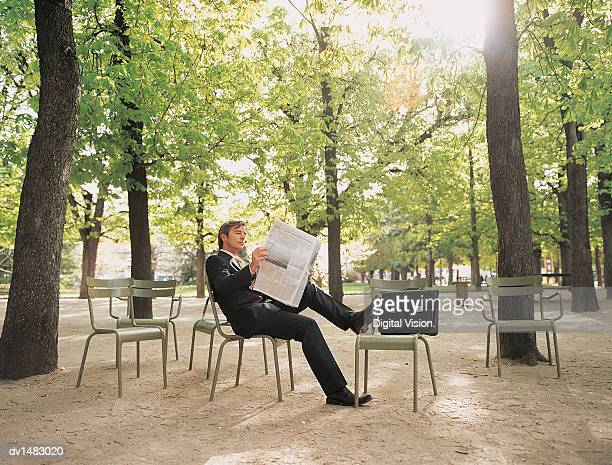 Businessman Sitting Reading Newspaper in Luxembourg Gardens, Paris
