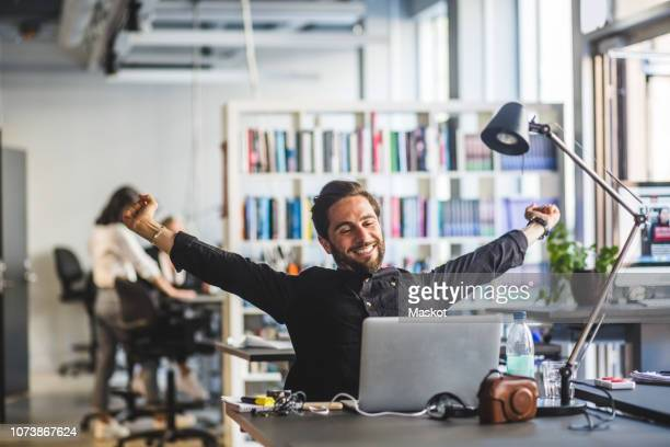 businessman sitting with arms outstretched at desk in office - ausgestreckte arme stock-fotos und bilder