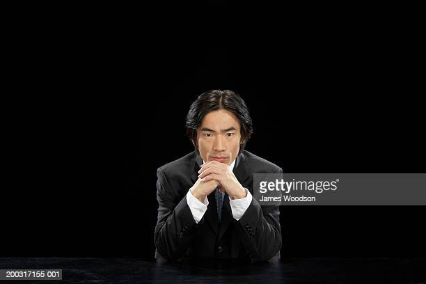 Businessman sitting with chin on hands, portrait