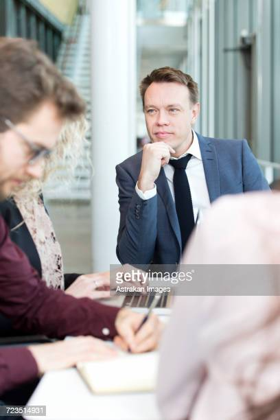 Businessman sitting with coworkers in meeting at office