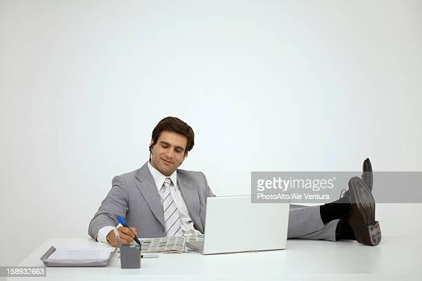 Businessman sitting with feet on desk, looking at newspaper