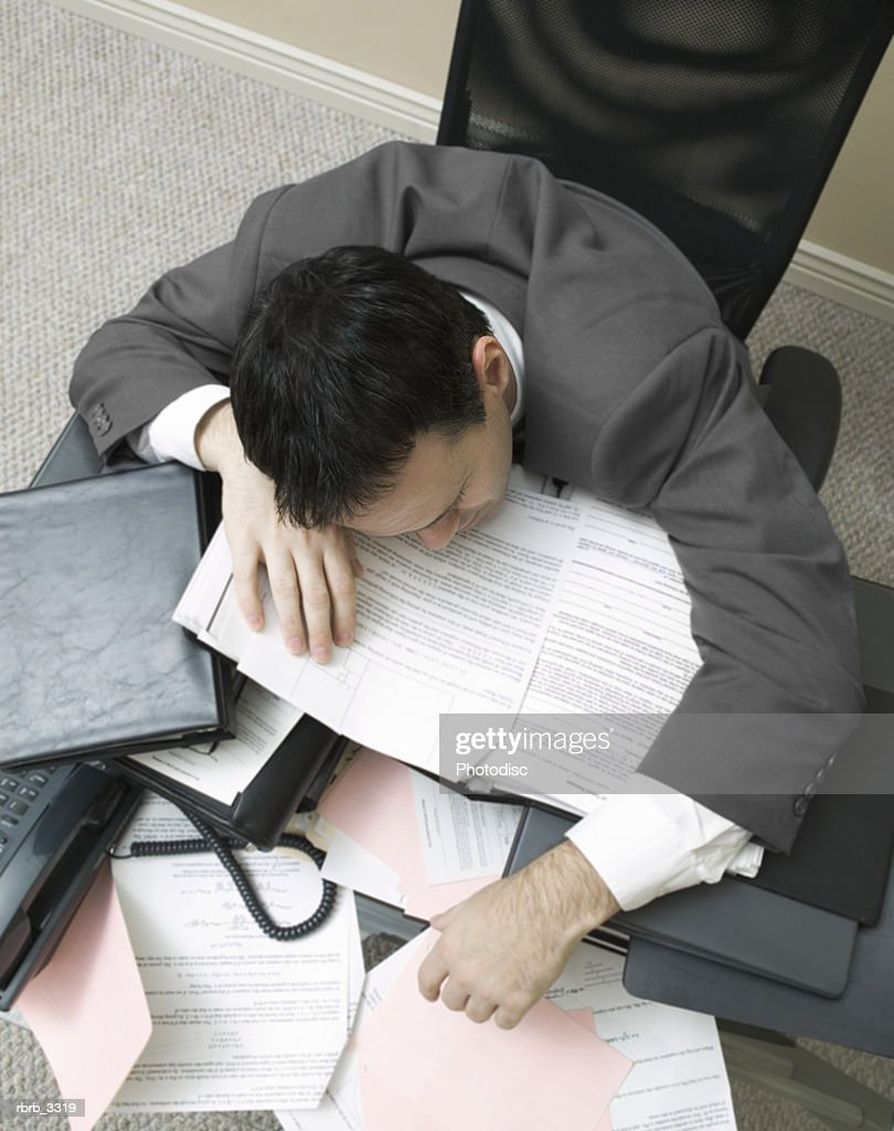 Businessman sitting with his head down on a desk : Foto de stock