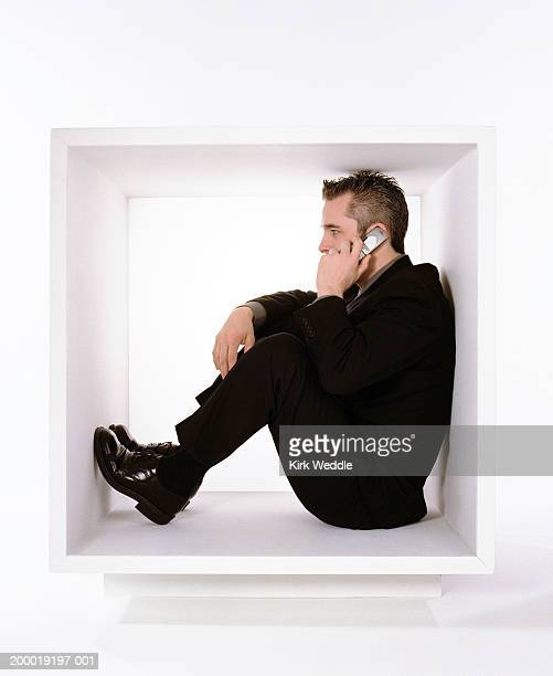 Businessman sitting within white box talking on mobile phone