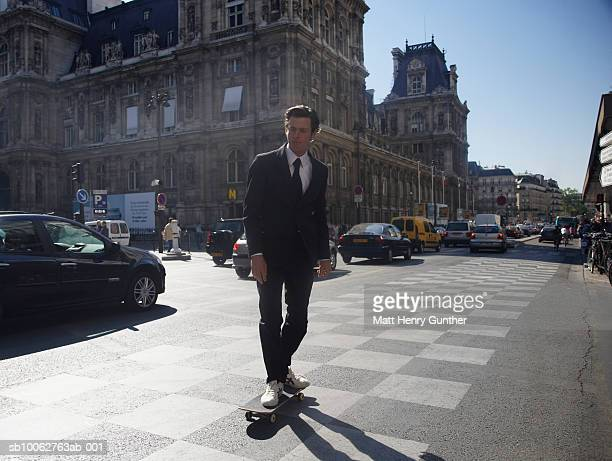 Businessman skateboarding in streets