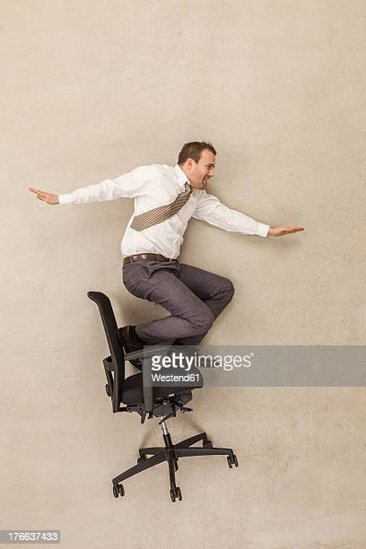 Businessman skating on office chair