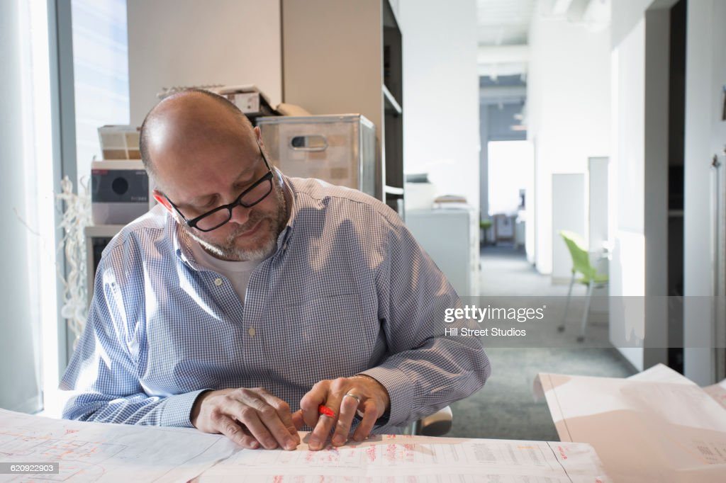 Businessman sketching blueprints in office : Stock Photo