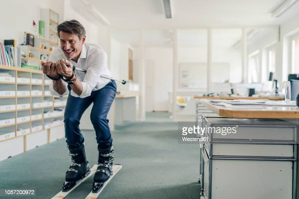 businessman skiing in office - ski holiday fotografías e imágenes de stock