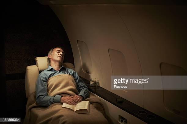 businessman sleeping aboard private jet - sonnecchiare foto e immagini stock