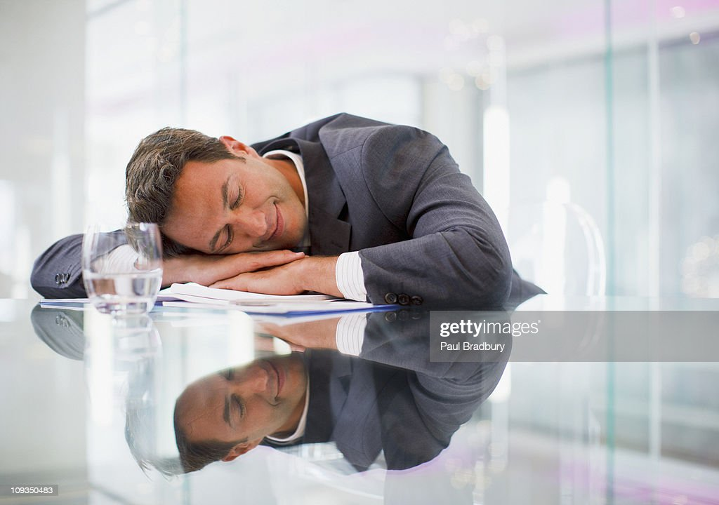 Businessman sleeping at desk in office : Stock Photo