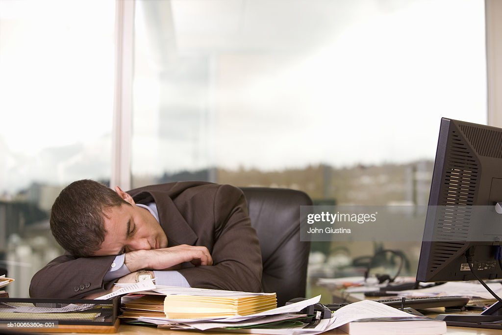 Businessman sleeping at desk in office : Foto stock