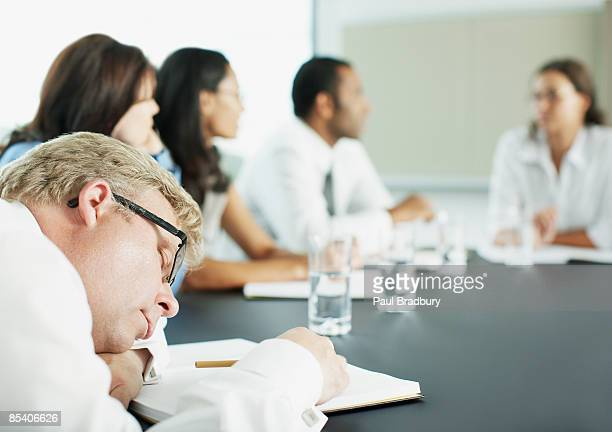 Businessman sleeping during meeting in conference room