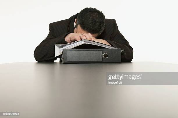 Businessman sleeping, his head laying on a stack of files