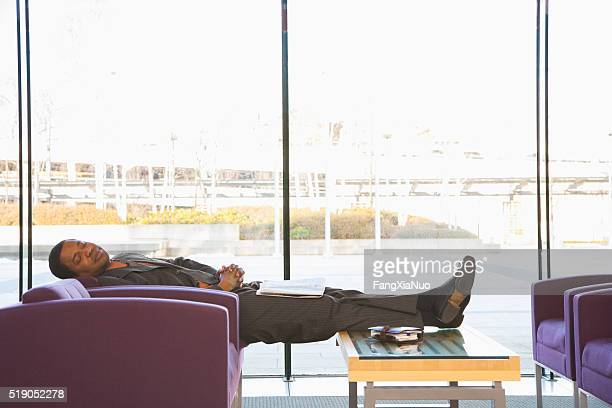 Businessman sleeping in a waiting area