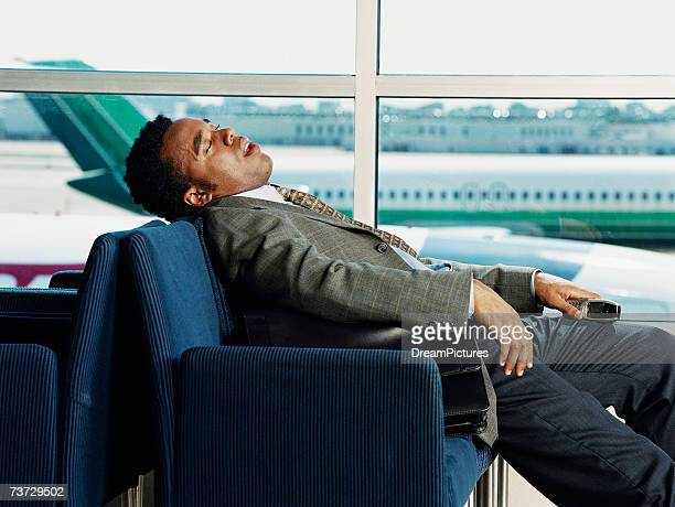 Businessman sleeping in airport lobby, side view