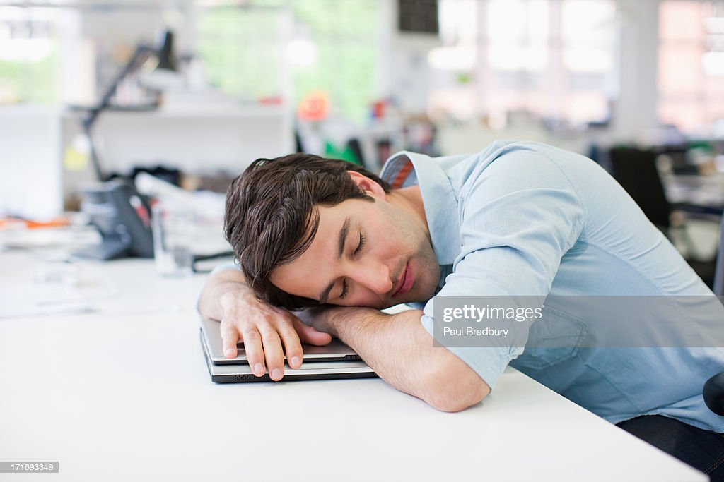 Businessman sleeping on laptop at desk in office : Stock Photo