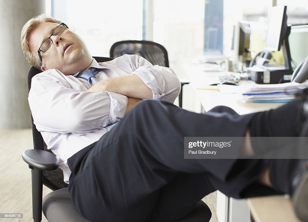 Businessman sleeping with feet up at desk : Stock Photo