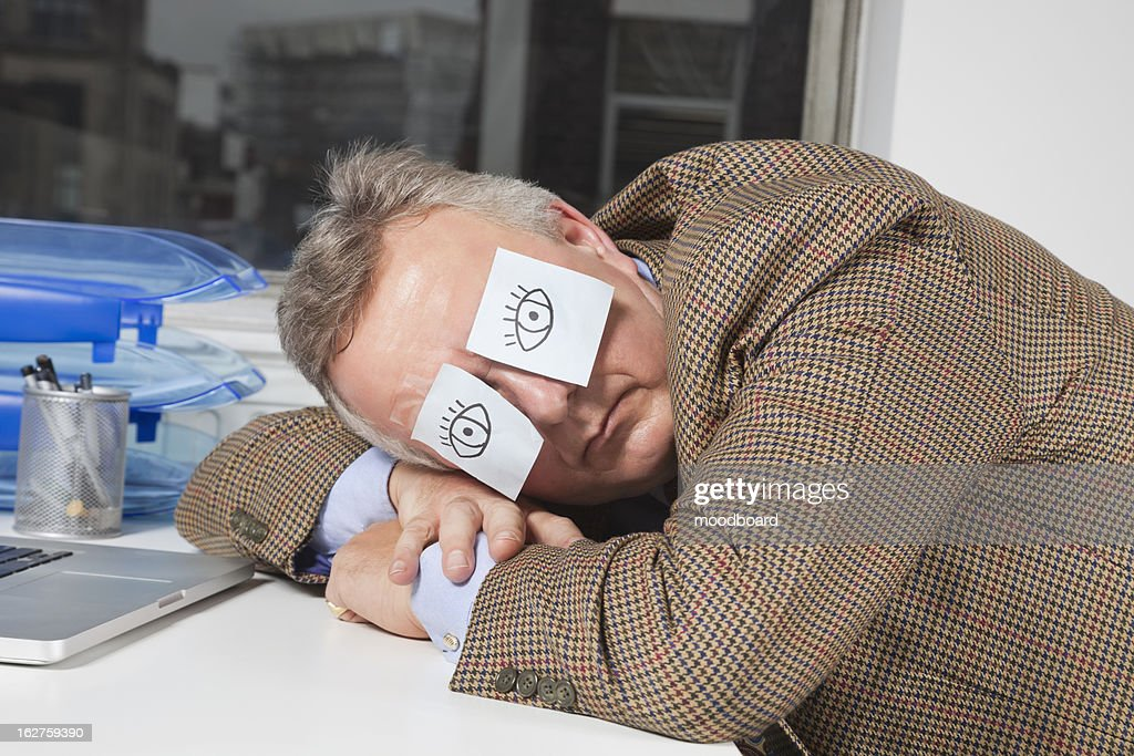 Businessman sleeping with sticky notes on eyes at desk in office : Stock Photo