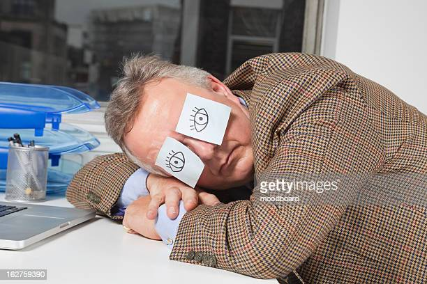 businessman sleeping with sticky notes on eyes at desk in office - dormir humour photos et images de collection