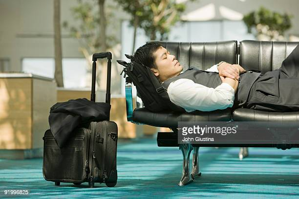 Businessman sleeps on chairs in airport.