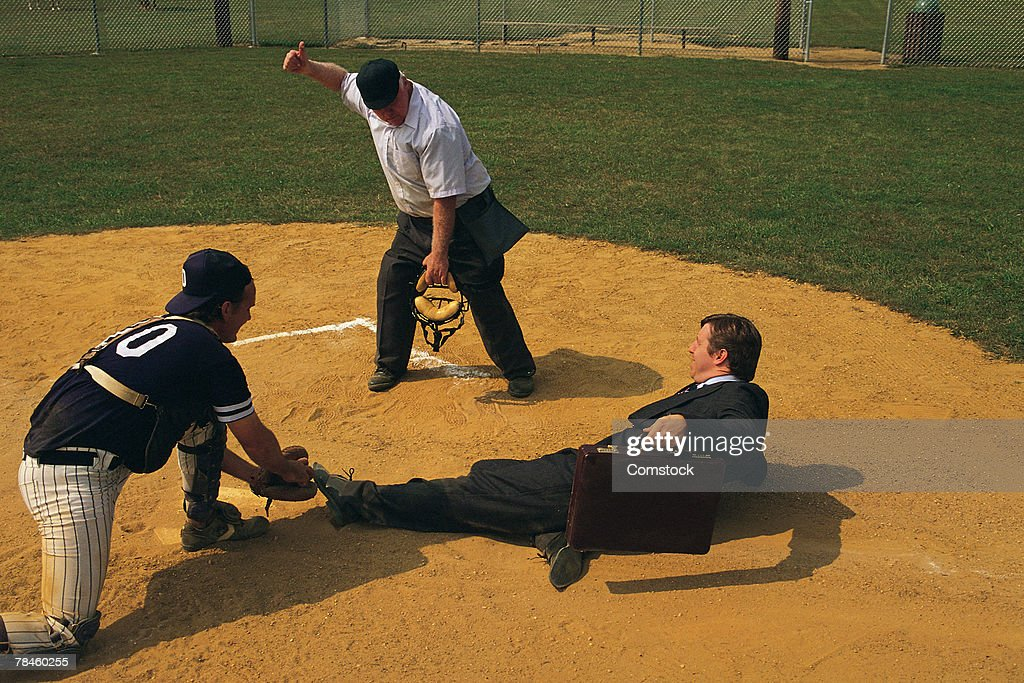 Businessman sliding into home plate is tagged out : Stock Photo