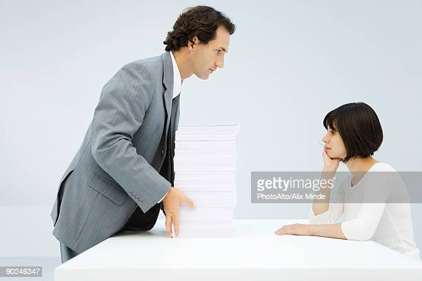 Businessman sliding tall stack of paper across a table to woman leaning on her elbow