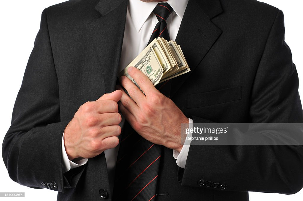 Businessman slipping stack of hundreds in his suit pocket : Stock Photo