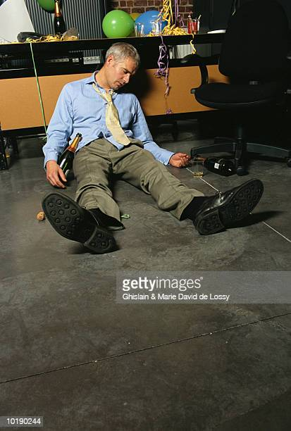 Businessman slumped on floor with champagne bottle