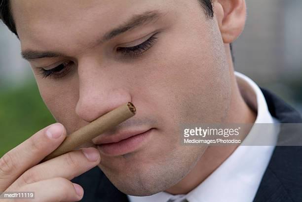 businessman smelling cigar, close-up - 葉巻 ストックフォトと画像
