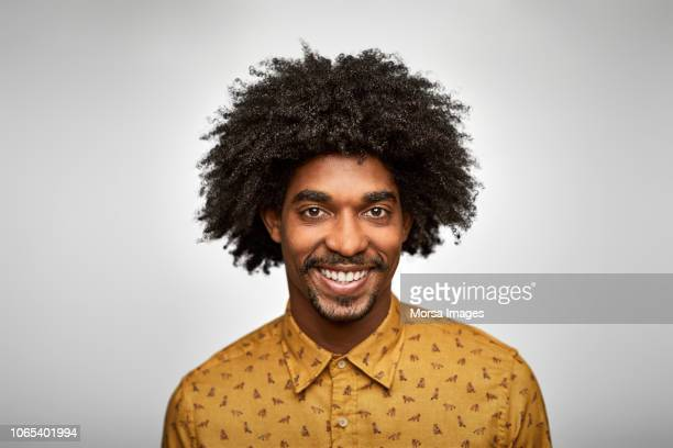 businessman smiling against white background - afro frisur stock-fotos und bilder
