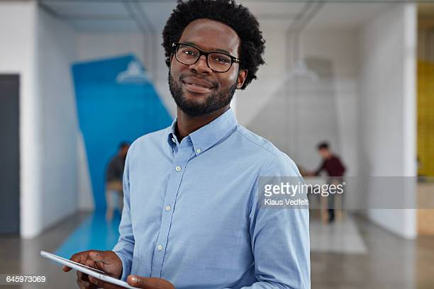 businessman smiling and holding tablet - blue shirt stock pictures, royalty-free photos & images