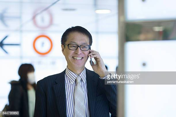 Businessman smiling and talking on mobile phone.