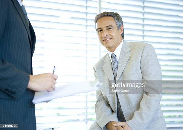 Businessman smiling at camera while colleague signs document