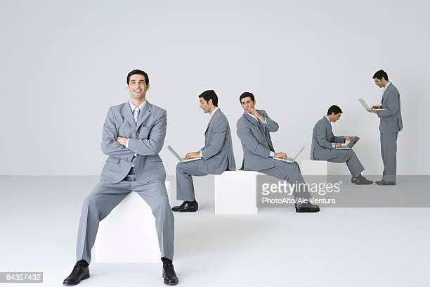 businessman smiling at camera with arms folded while his clones use laptops in background - middelgrote groep mensen stockfoto's en -beelden