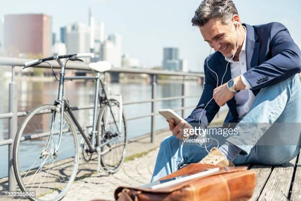 businessman smiling at video call through mobile phone while sitting on bench - hesse duitsland stockfoto's en -beelden