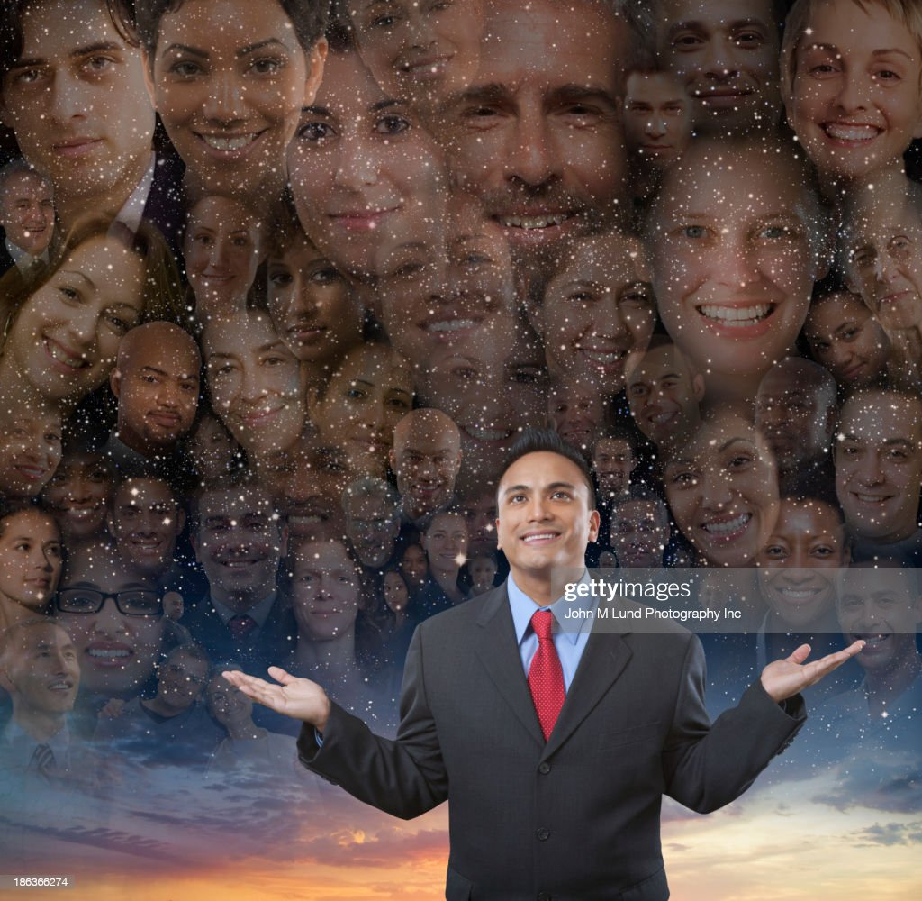 Businessman smiling by montage of smiling faces : Stock Photo
