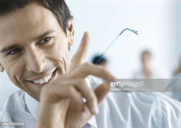 Businessman smiling, holding glasses, gesturing
