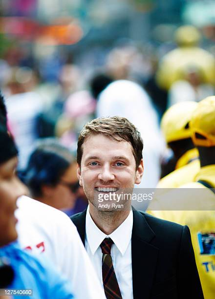 Businessman smiling in city crowd.