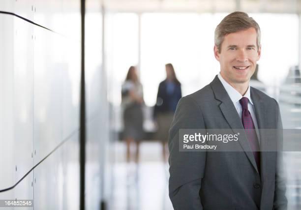 Geschäftsmann lächelnd im Büro-Korridor