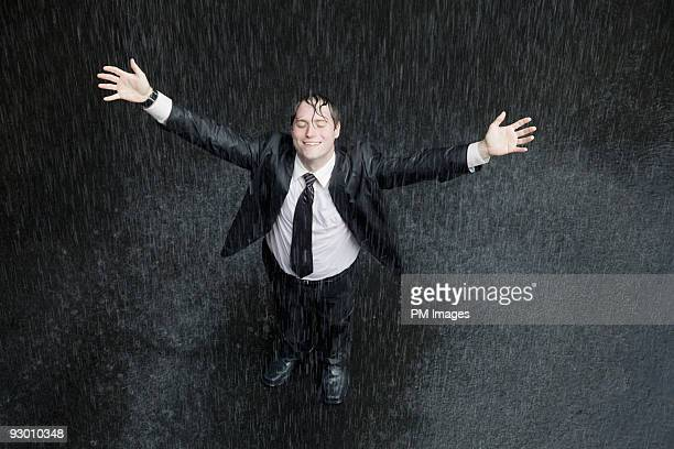 Businessman smiling in rain