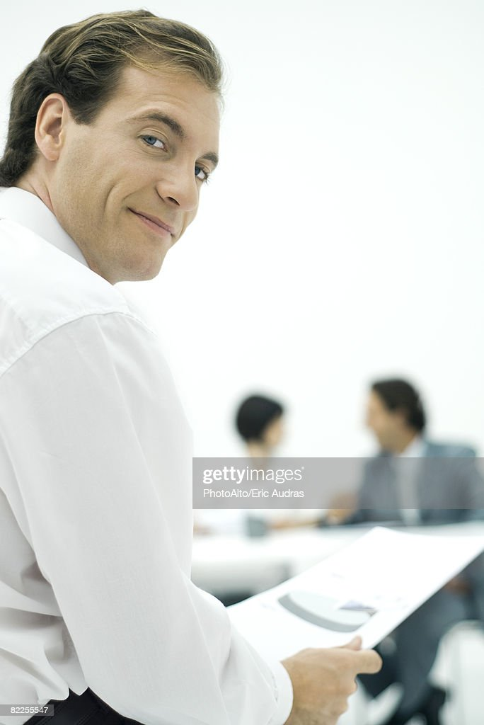Businessman smiling over shoulder at camera, holding document, colleagues in background : Stock Photo