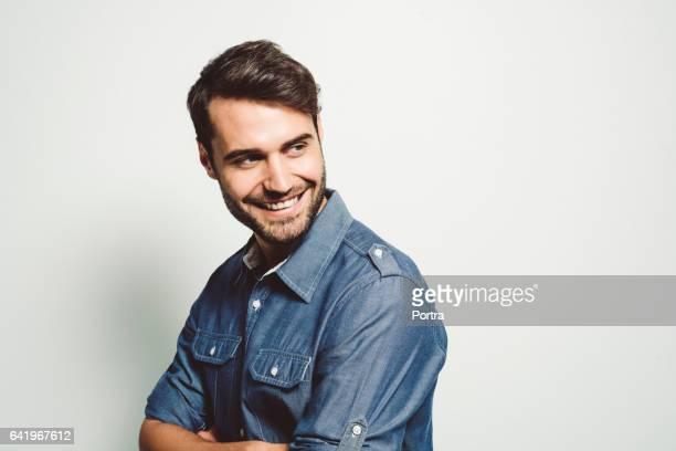 empresário, sorrindo enquanto a desviar o olhar sobre branco - só um homem jovem - fotografias e filmes do acervo