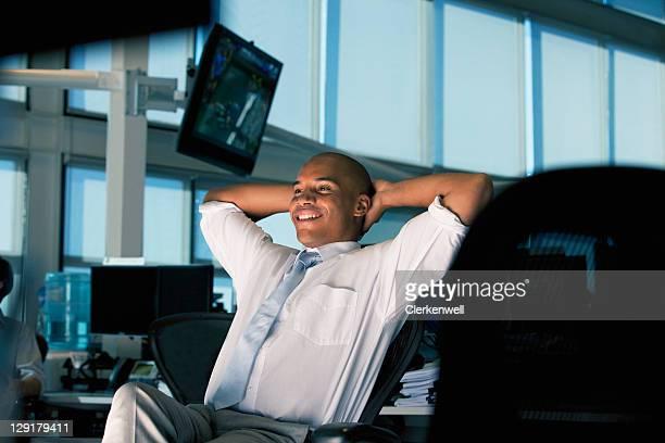 Homme d'affaires souriant tout en vous relaxant dans le bureau