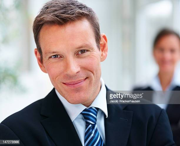 Businessman smiling with colleagues in the background