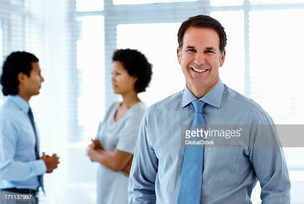 Geschäftsmann lächelnd mit Kollegen im Hintergrund stehen