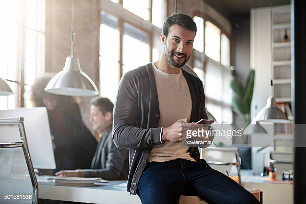 Lächelnd Geschäftsmann mit Handy sitzen an seinem Schreibtisch