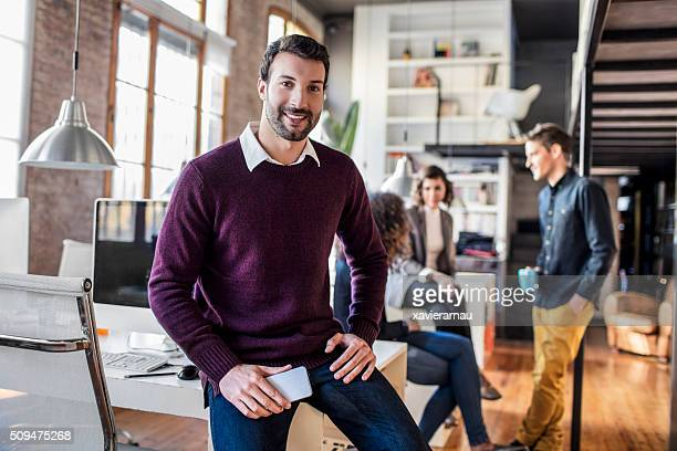 businessman smiling with mobile phone sitting on his desk - 20 29 years stock pictures, royalty-free photos & images