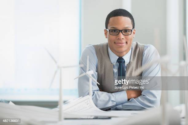 Businessman smiling with wind turbine models