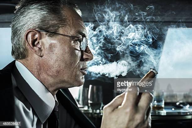 Geschäftsmann Rauchen Sie eine Zigarre in einer limousine.