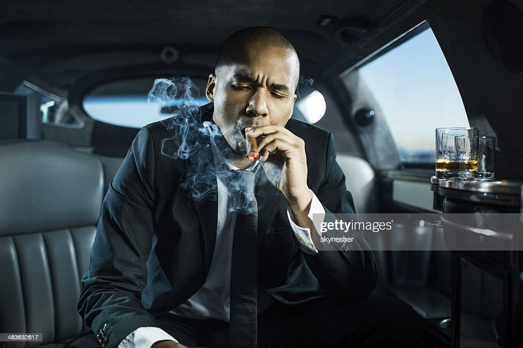 Businessman Smoking A Cigar In Limousine Stock Photo