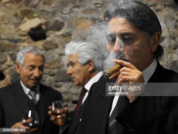 Businessman smoking cigar in restaurant, businessmen in background